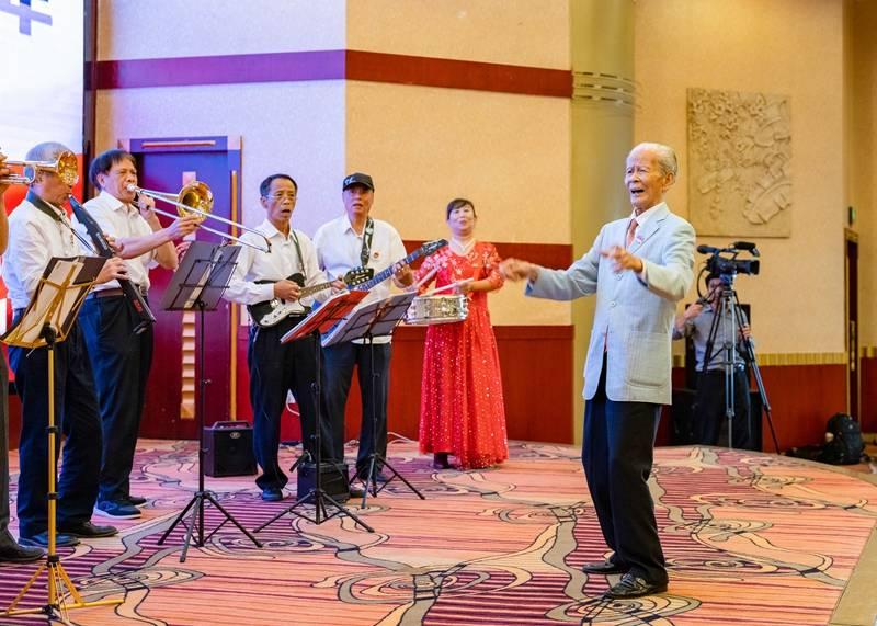 """06来自老三届的父辈,九十八岁的李老先生,指挥管弦乐,及全场,唱响""""老三届登山队之.jpg"""